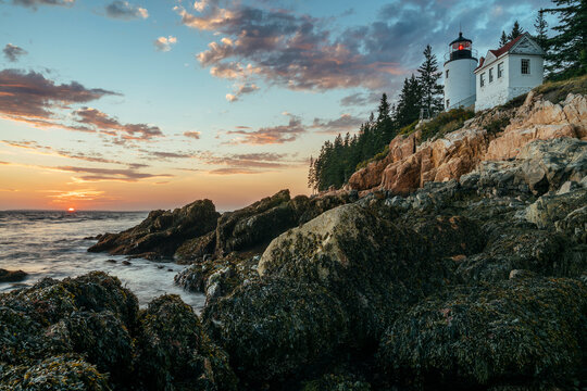 View of lighthouse on coast in Acadia National Park during sunset