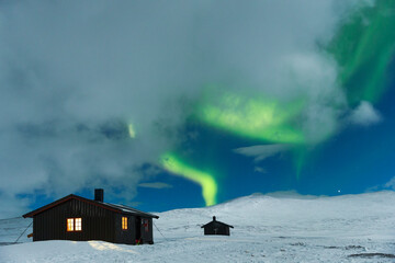View of Aurora Borealis over cabins on snowy landscape