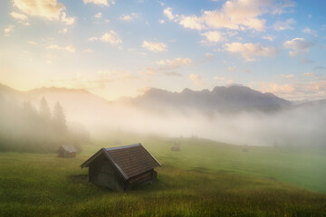 View of cabin on grassy landscape during foggy sunrise