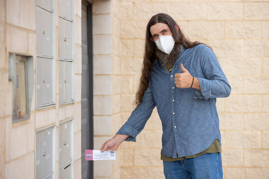 Caucasian male with long hair and full beard wearing a mask and putting official election mail in ballot in the outgoing mail slot at his apartment building