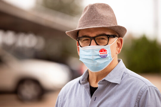 Older Caucasian male with glasses and fedora, wearing a mask and an I Voted Today sticker on the mask