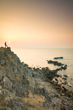 Man standing on cliff by coastline during sunset