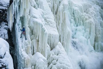 Ice climber climbing frozen waterfall