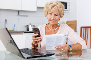 Attractive mature woman talking on phone, using her laptop and holding handbook