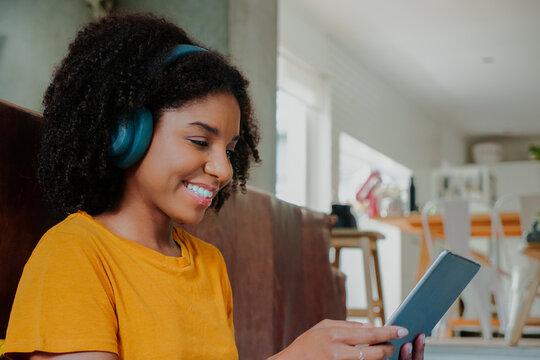 African American teenage female wearing headphones listening to music scrolling on digital tablet sitting in comfortable lounge.