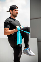 Handsome Hispanic man warming up with elastic resistance band before exercise outdoors at rooftop - home open air work out concept
