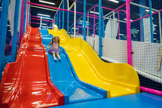 Happy little baby, 4 year old girl, children ride up, down slide in play center