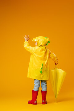 small child in a raincoat, rubber boots and an umbrella in yellow background
