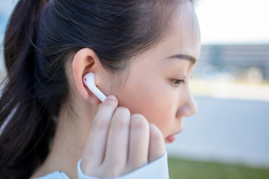 Woman putting earphones before exercise.