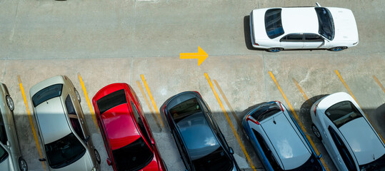 Top view of car parked at concrete car parking lot with yellow line of traffic sign on the street....