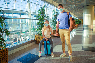 Dad and little girl with nedical masks at airport. Protection against Coronavirus and gripp