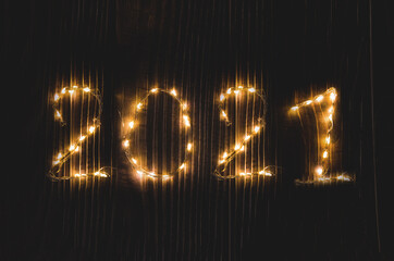 numbers 2021 from a glowing garland on a black background