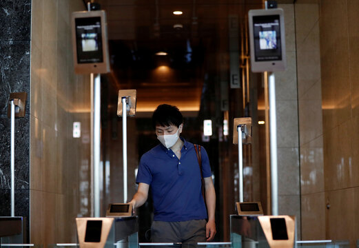 A man wearing a protective face mask demonstrates the facial recognition and elevator navigation systems, at the entrance hall of SoftBank's new headquarters building in Tokyo