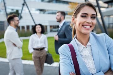 Portrait of smiling businesswoman standing in front of modern office buildings looking at camera with colleagues behind her.