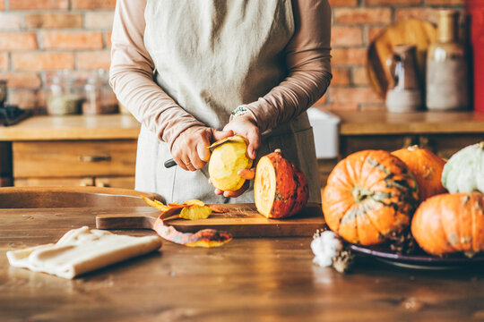 Female hands with knife chopping pumpkin on cutting board. Preparing autumn vegetables.