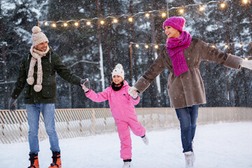 christmas, family and leisure concept - happy mother, father and daughter at outdoor skating rink...