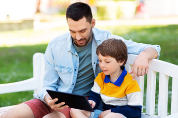 family, fatherhood and technology concept - happy father and little son with tablet pc computer sitting on bench at summer park