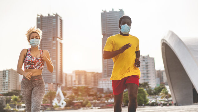 Young multiracial fit friends running outdoor while wearing face protective masks during coronavirus outbreak - Main focus on  faces