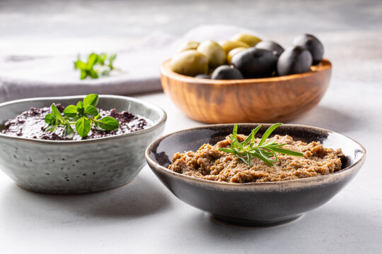 Tapenade - paste made from olives. Bowls with spreadable black and green olive cream on concrete background.