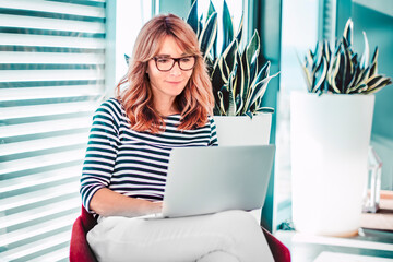 Attractive woman working on laptop in modern office