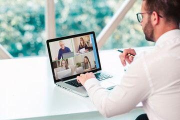 Rear view shot of businessman having discussion and online meeting in video call