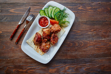 Shashlik, meat cooked on skewers on an open table, in a white plate on a wooden background