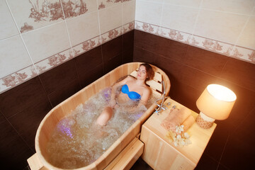 A young girl enjoys an eco-friendly wooden Jacuzzi bath