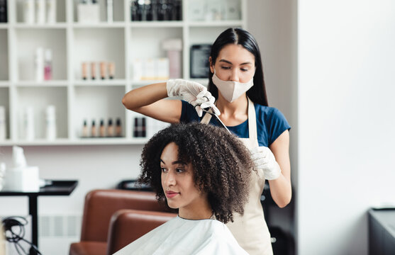 Hairdresser in protective mask cutting hair of curly african american client in beauty salon