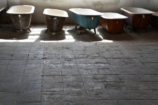 ausrangierte Badewannen stehen in Reihe in einer Industrieruine