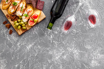 Fototapete - Wine appetizer. Toasts, nuts, olives on grey desk top view copy space