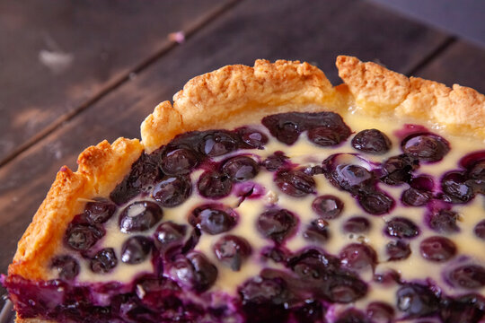 Edge of rustic shortbread pie with blueberries in sour cream filling on a wooden background with piece cut off
