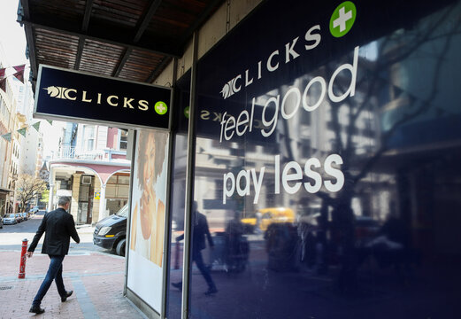 A man walks past a closed branch of  Clicks stores following protests in Cape Town