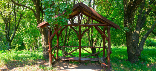 Wooden arbor in the forest. Wide photo.