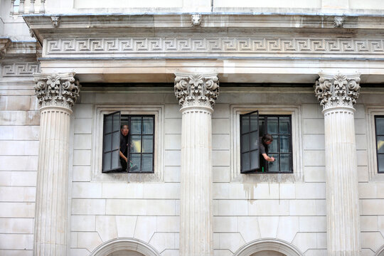 Workers clean windows at the Bank of England in London