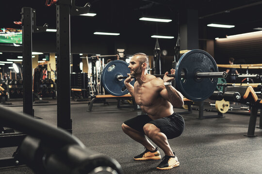 Bodybuilder during his workout with a barbell in the gym
