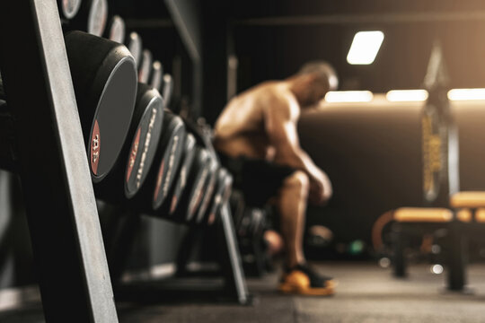 Dumbbells with free space and blurred bodybuilder on background