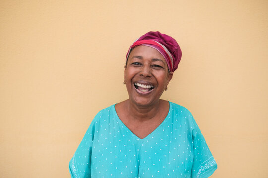 Happy african senior woman laughing and looking in camera - Portrait of real and authentic person wearing traditional dress