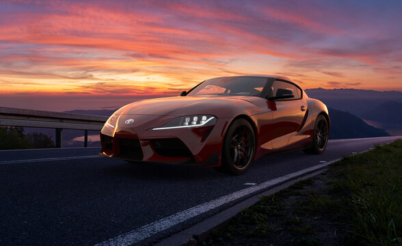 Toyota Supra during a dynamic drive on a scenic road after sunset