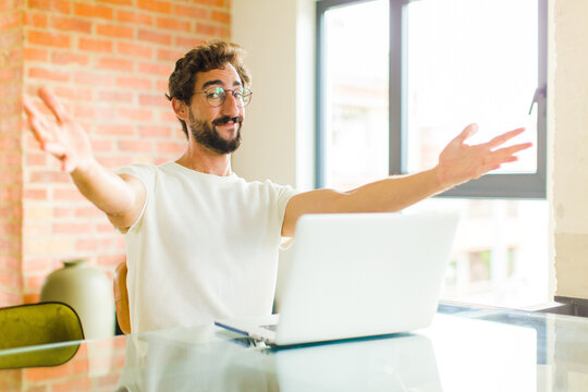 young bearded man with a laptop smiling cheerfully giving a warm, friendly, loving welcome hug, feeling happy and adorable