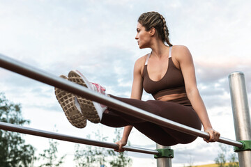 Woman athlete during calisthenics workout on a parallel bars