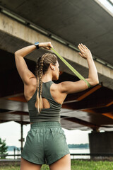 Athletic woman during workout with a resistance rubber band on a street