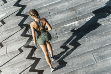 Sportive woman is running upstairs by a concrete staircase