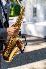 Young man playing the saxophone at the wedding. Blurred background. Selective focus.