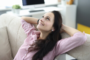 Woman sits on couch with her arms folded behind her head and looks up dreamily. Positive affirmations to lift your mood concept