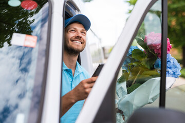 Courier inside the white van during flowers delivery is waiting for a client