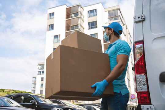 Delivery man wearing prevention mask and gloves is holding stack of the cardboard boxes