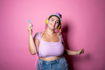 Young plus size woman on pink background dancing holding smartphone - Chubby woman listening steaming music isolated studio shot