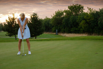 Lady Focused On Hitting Ball Into Golf Hole .