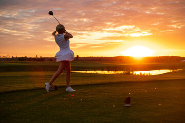 Woman Hit Ball With Golf Stick at Sunset Background .