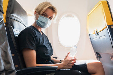 Printed roller blinds Akt Woman wearing prevention mask during a flight inside an airplane